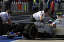 Sergio Perez is wheeled back in to the Sauber garage