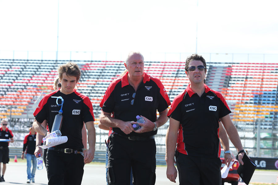 John Booth walks the track with members of his Marussia team