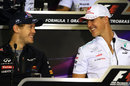 Michael Schumacher and Sebastian Vettel share a joke in the driver press conference