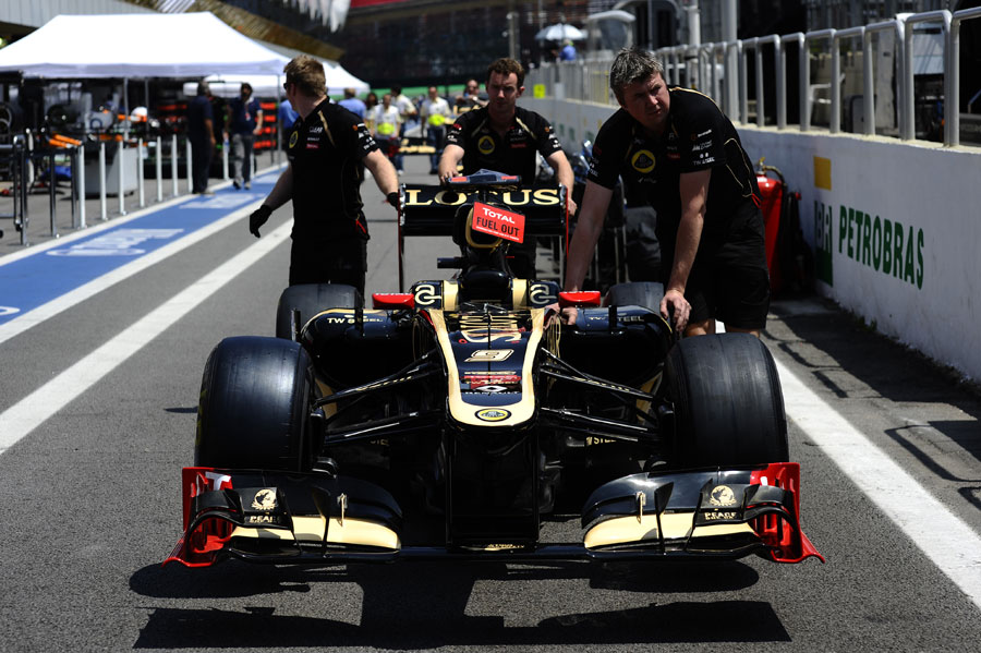 A Lotus E20 is pushed down the pit lane