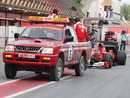 Fernando Alonso's Ferrari is towed back to the pits
