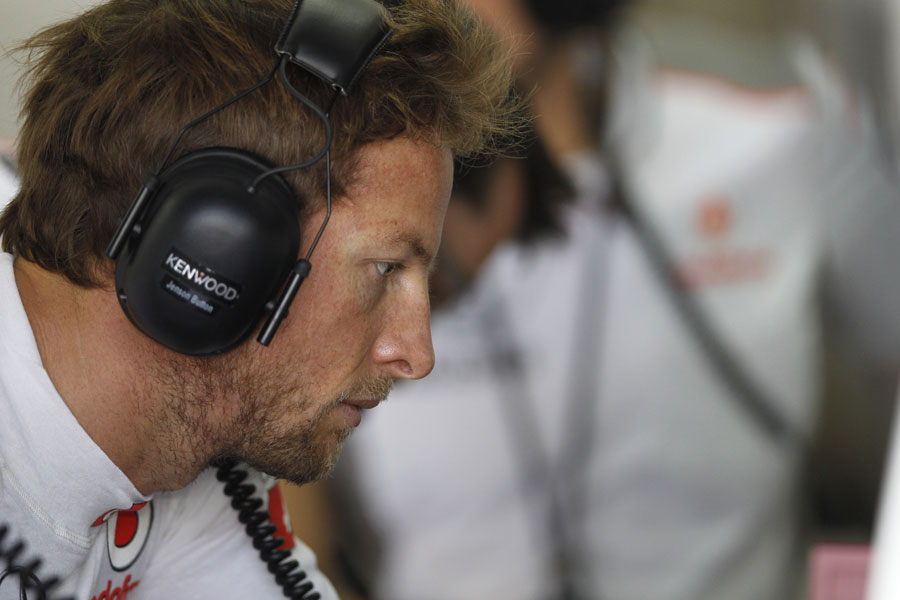 Jenson Button studies data in the McLaren garage