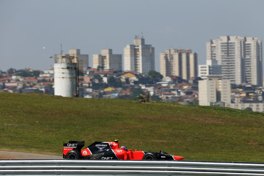 Charles Pic on track in front of the Sao Paulo skyline