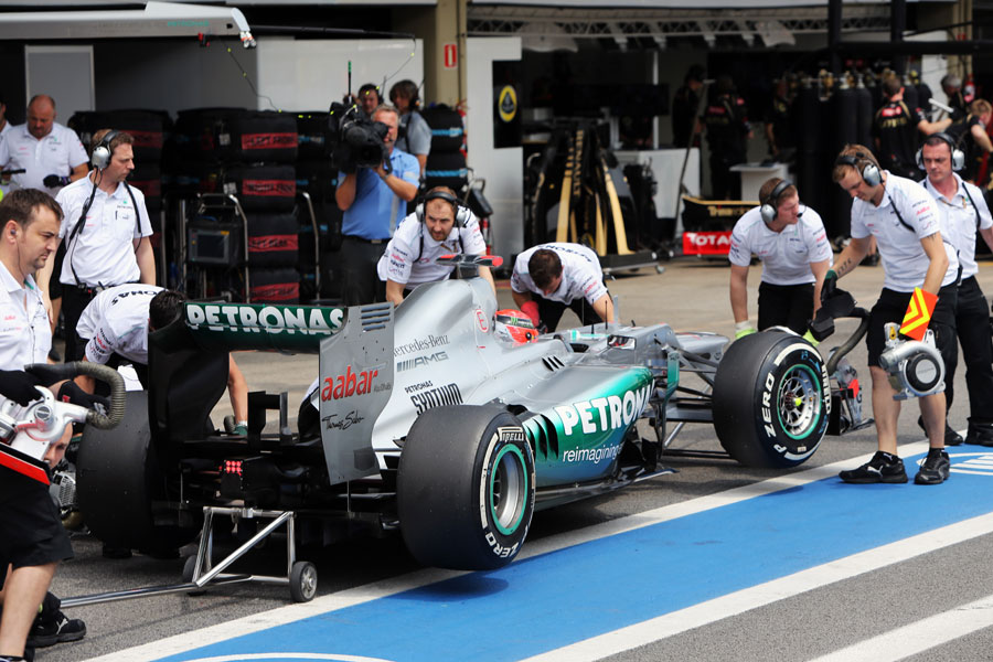 Michael Schumacher is wheeled in to the garage after being eliminated from Q2