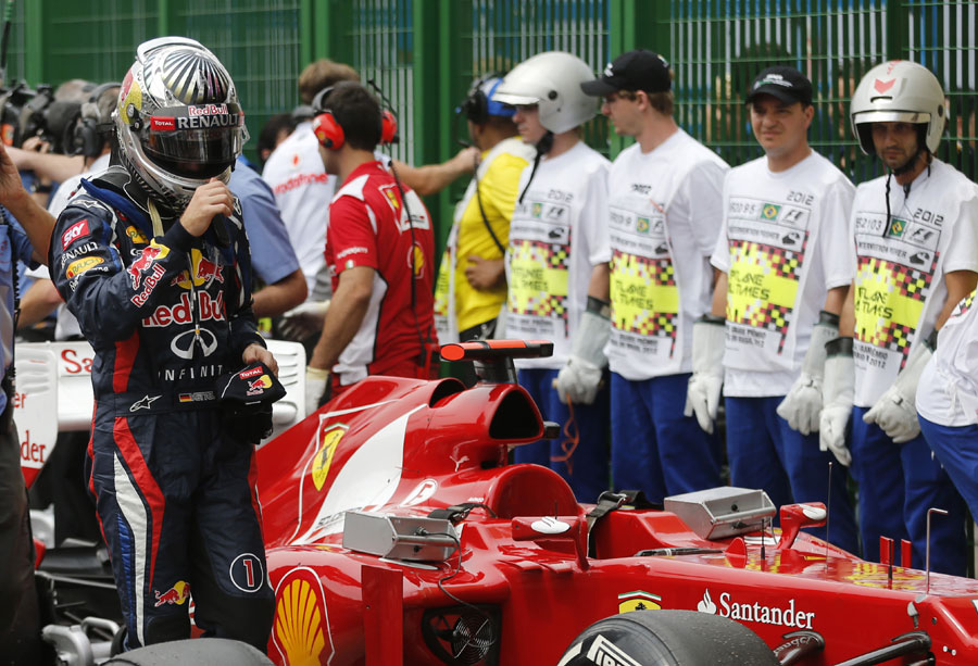 Sebastian Vettel walks past a Ferrari after qualifying fourth