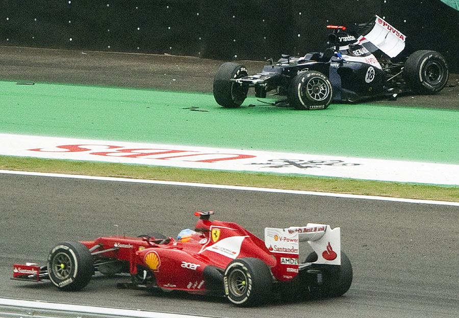 Fernando Alonso passes by Pastor Maldonado's crashed Williams