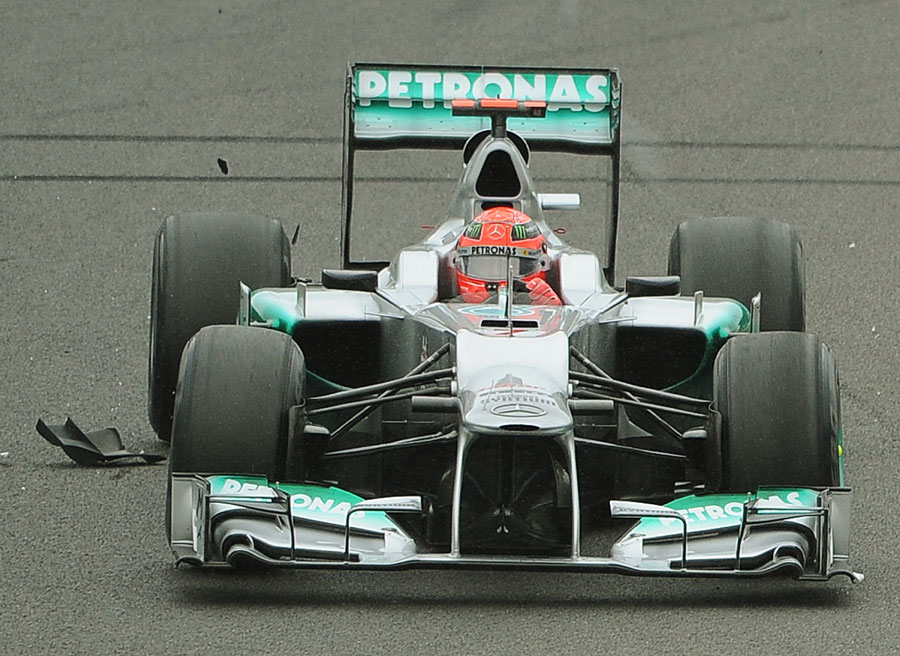 Michael Schumacher drives over debris on his way to seventh place in his final race