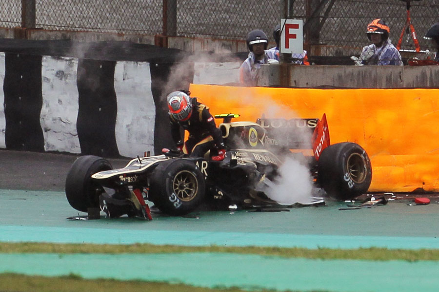 Romain Grosjean pulls himself out of his wrecked Lotus
