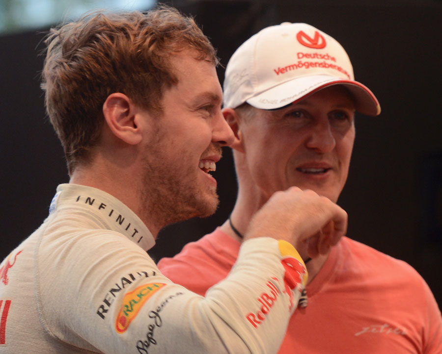 Sebastian Vettel and Michael Schumacher share a joke at the Race of Champions