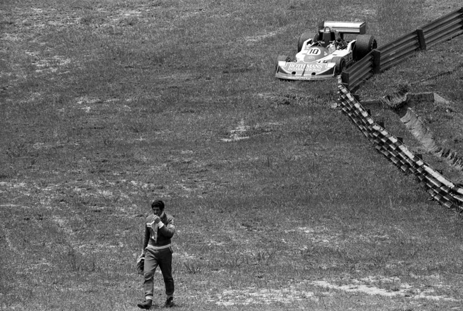 Jody Scheckter retires from the race with his brother Ian's stricken car in the background