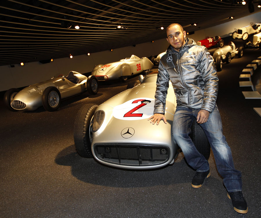 Lewis Hamilton poses for a photo with the championship-winning Mercedes W196