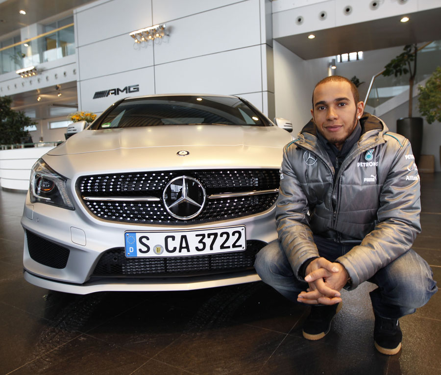 Lewis Hamilton poses with a Mercedes road car