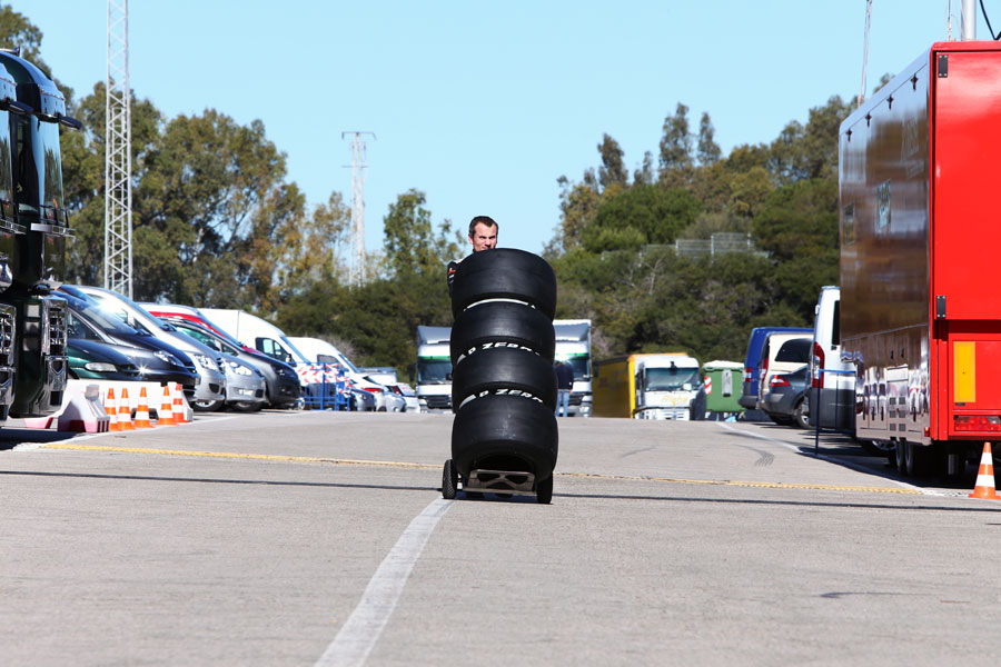 An McLaren mechanic wheels some new Pirelli tyres through the paddock