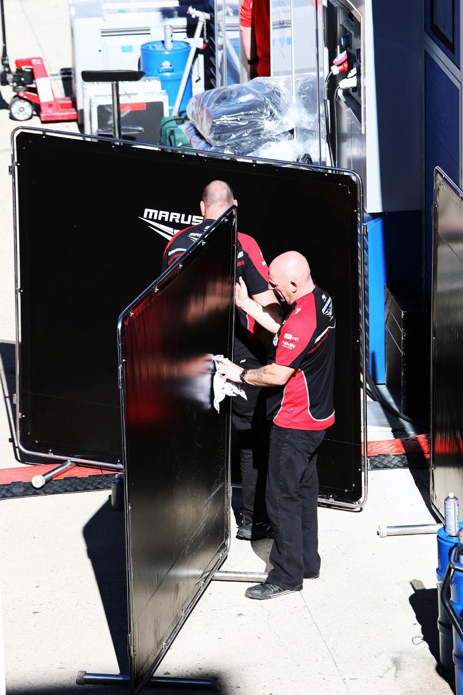 Marussia mechanics clean screens in the paddock