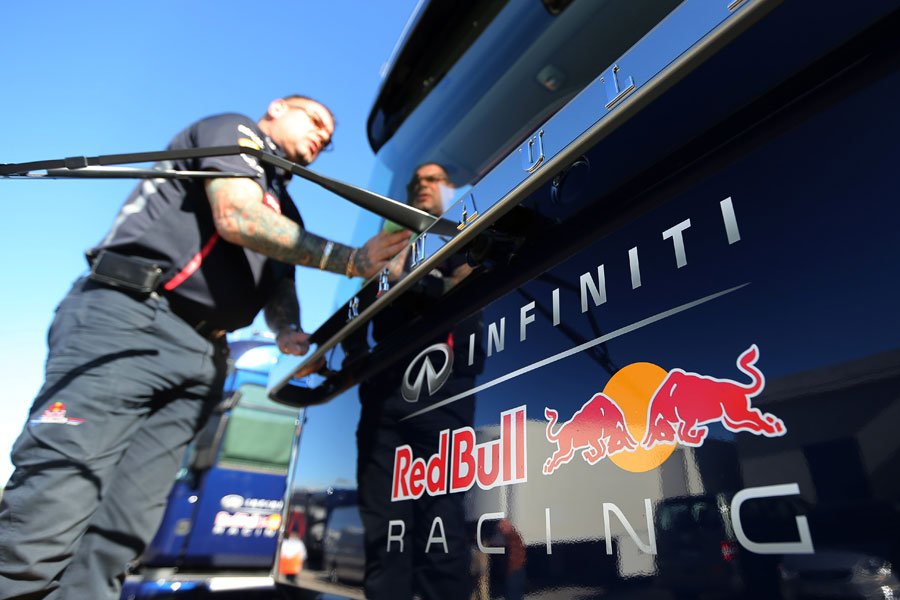 A Red Bull mechanic cleans a team transporter