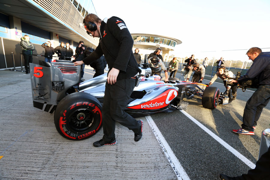 Jenson Button is wheeled back in to the McLaren garage
