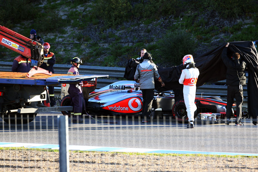 Jenson Button helps McLaren cover the MP4-27 after stopping on track