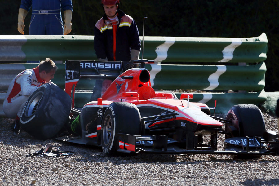Max Chilton inspects the right rear suspension of his MR02 after spinning off in to the gravel