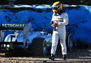 Lewis Hamilton walks away from his car after crashing at turn six
