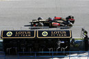 Romain Grosjean flashes past the Lotus pit wall