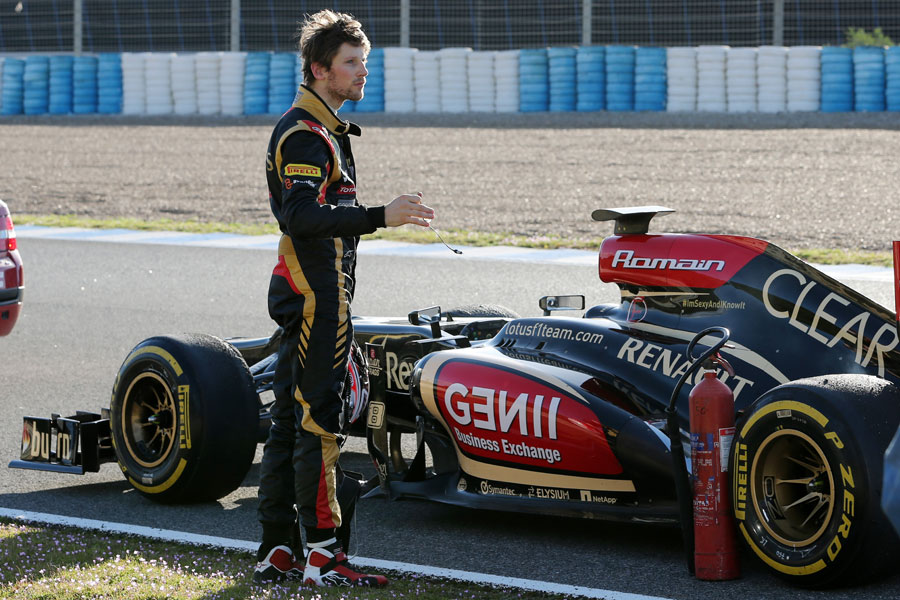 Romain Grosjean stands by his car after it ran out of fuel at the end of the day