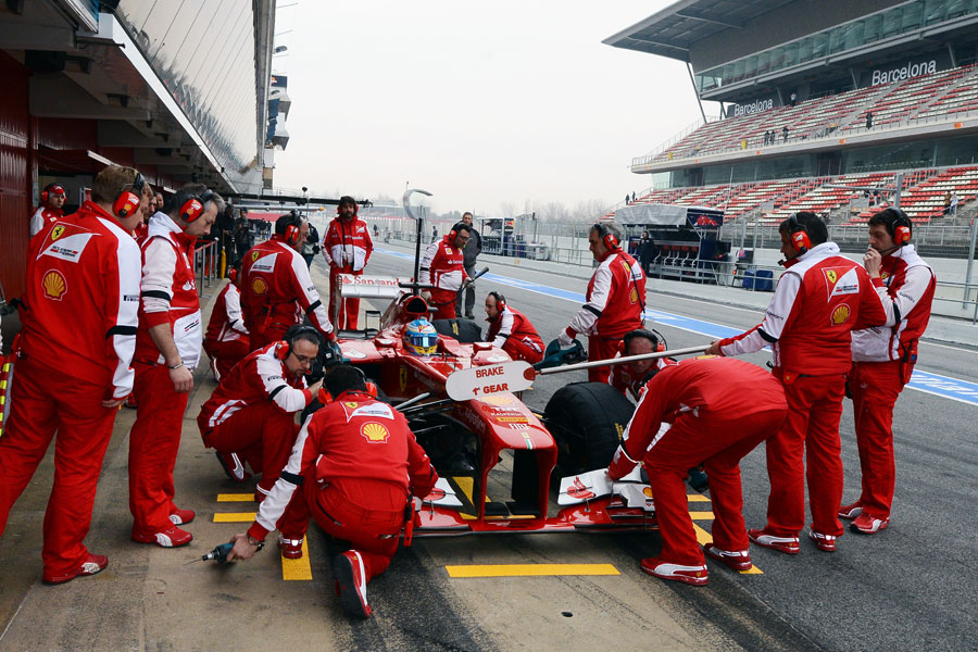 The Ferrari pit crew gather around Fernando Alonso's car
