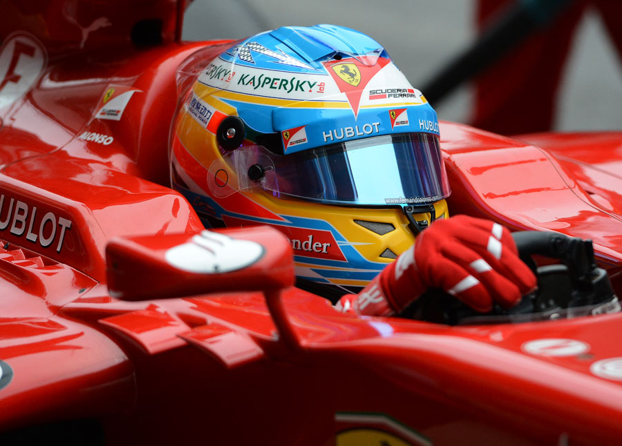 Fernando Alonso returns to the garage in the Ferrari