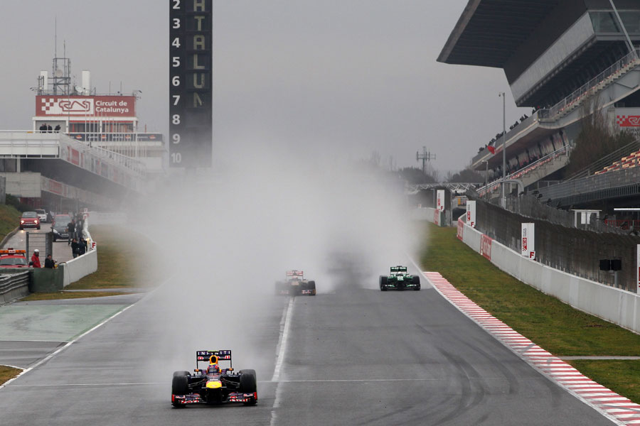 Mark Webber exits the pits leaving spray in his wake