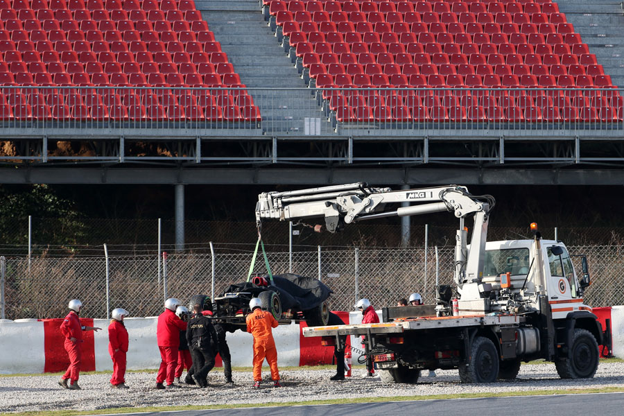 Romain Grosjean's Lotus is recovered from the gravel after he spun off
