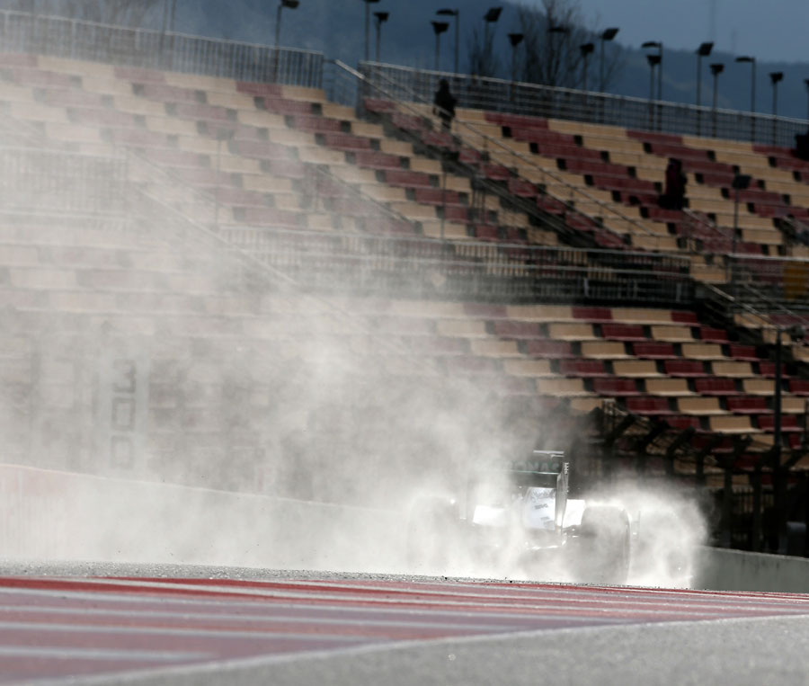 Lewis Hamilton leaves a trail of spray behind him on the pit straight