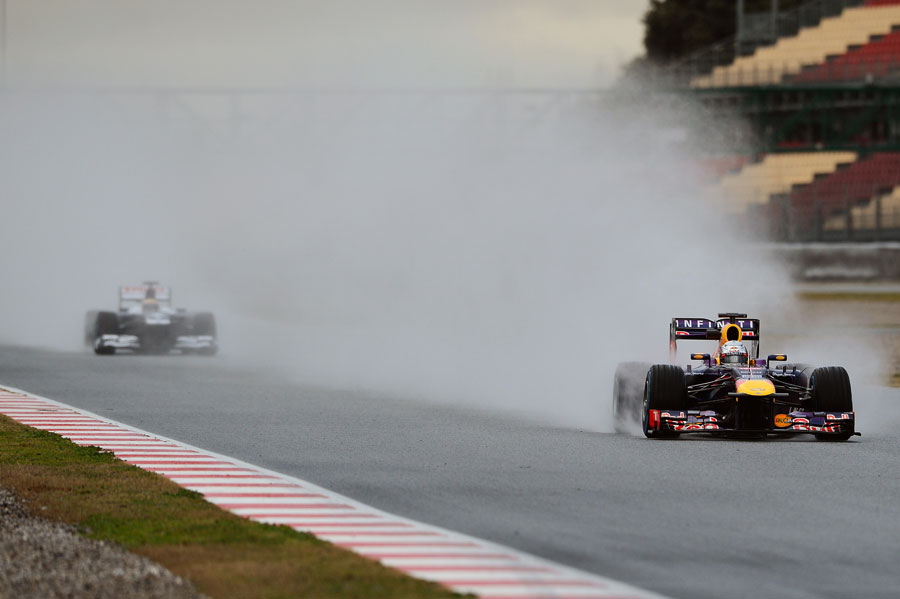 Sebastian Vettel leaves Pastor Maldonado in a cloud of spray