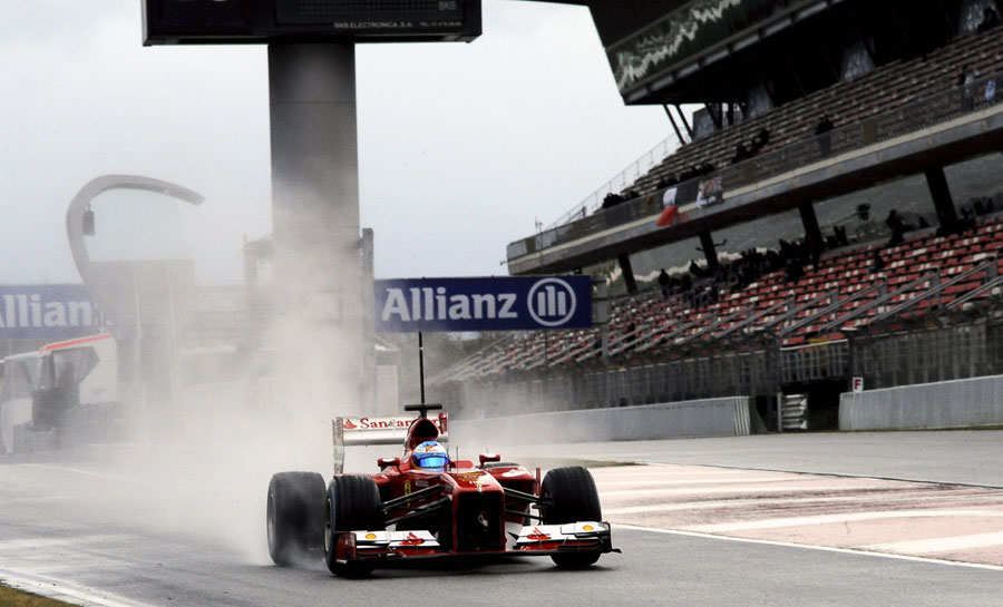 Fernando Alonso leaves the pits on full wet tyres