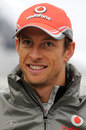 Jenson Button talks to the media in the paddock