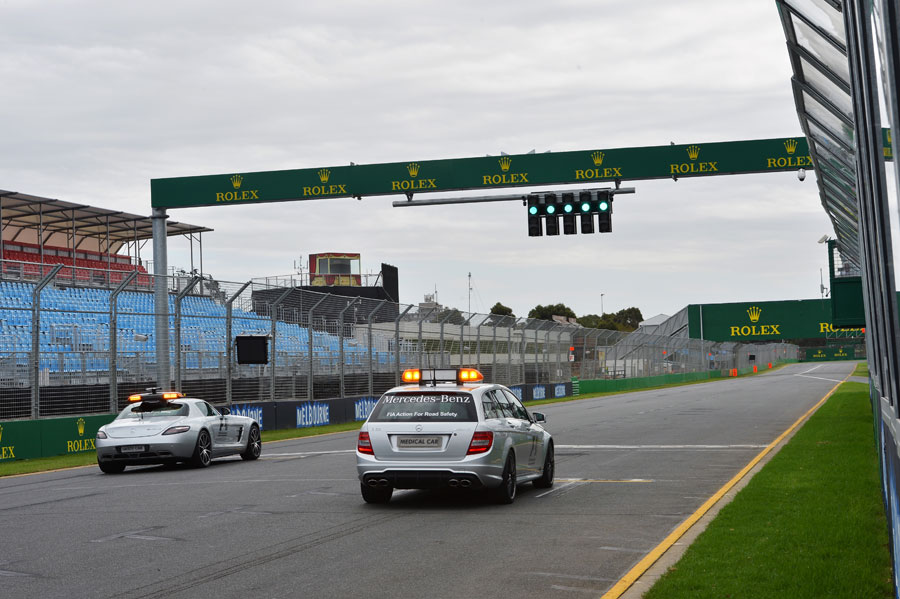 The medical car and safety car prepare to complete laps of the track