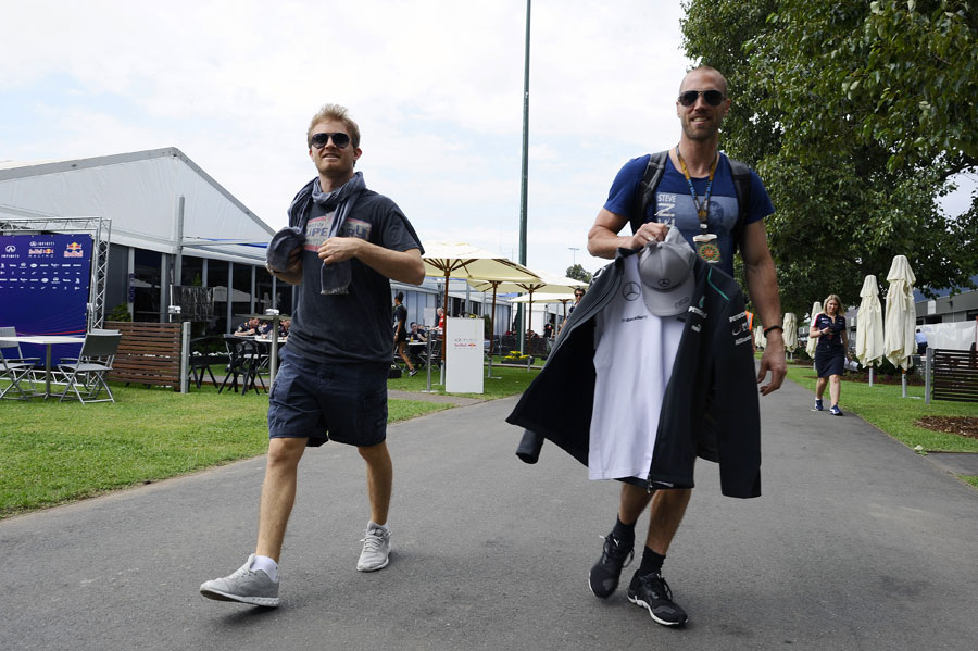 Nico Rosberg walks through the paddock with his trainer