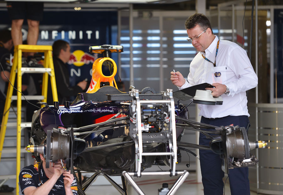 A member of the FIA checks over one of the Red Bulls