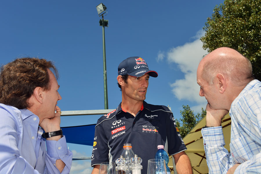 Mark Webber speaks to Christian Horner and Adrian Newey in the paddock