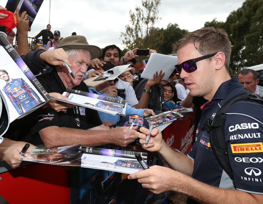Sebastian Vettel signs autographs as he arrives in the paddock