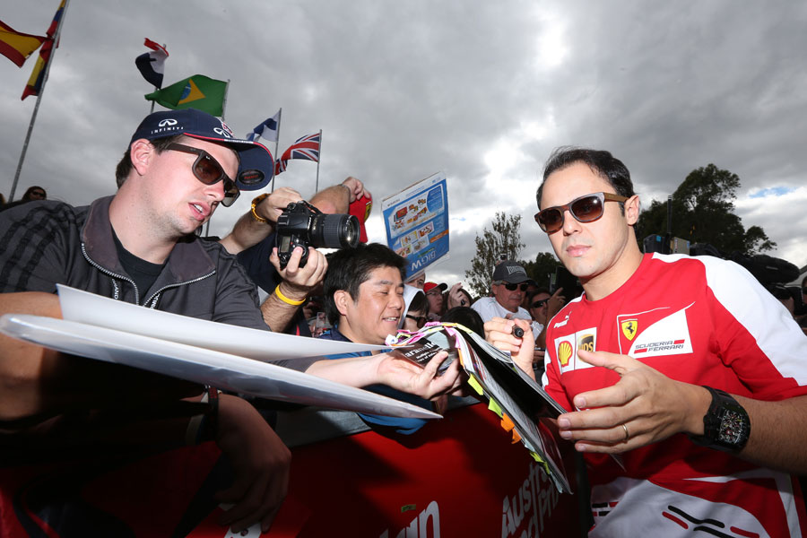 Felipe Massa signs autographs as he arrives in the paddock