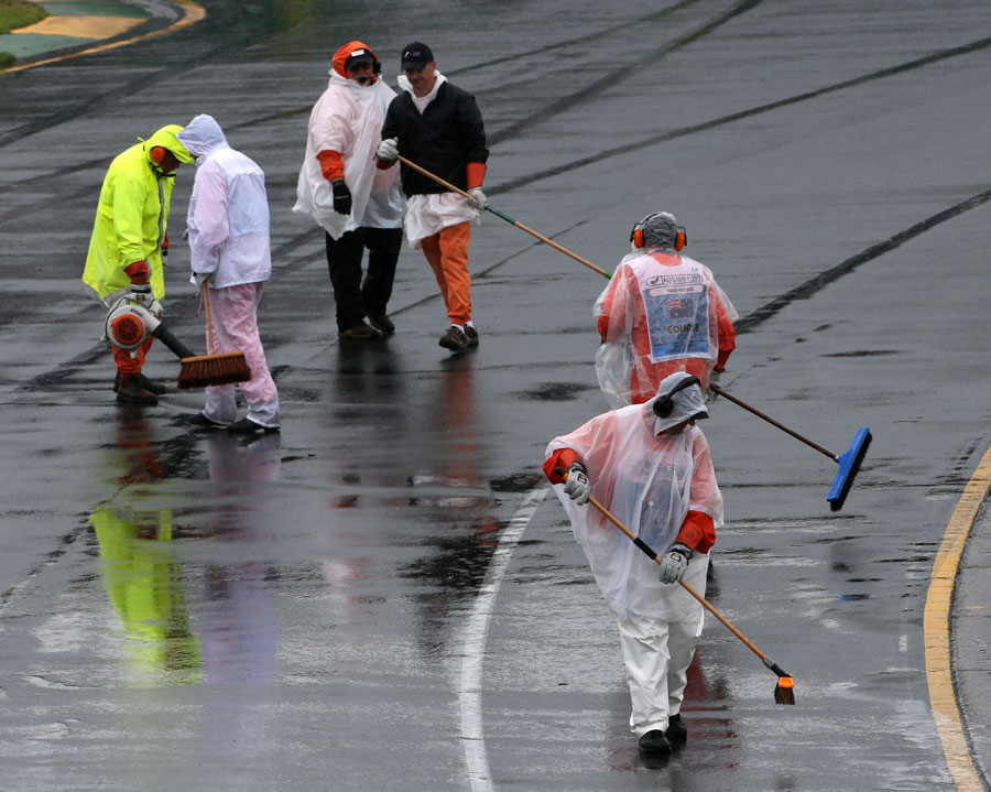 The story of the day as marshals try to sweep water off the track