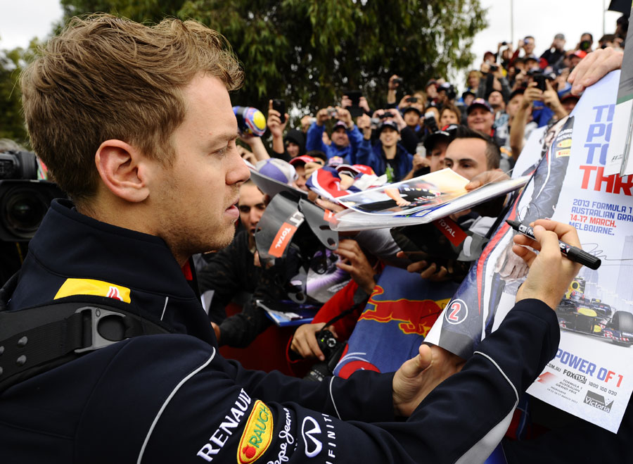 Sebastian Vettel signs a Mark Webber poster for fans