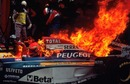 Eddie Irvine's Jordan goes up in flames during a pit stop