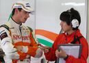 Adrian Sutil talks with a Bridgestone tyre technician