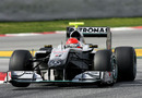 Michael Schumacher lifts a wheel in the Mercedes