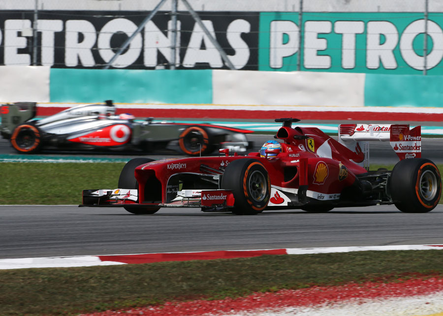 Fernando Alonso tackles turn two, followed by Jenson Button