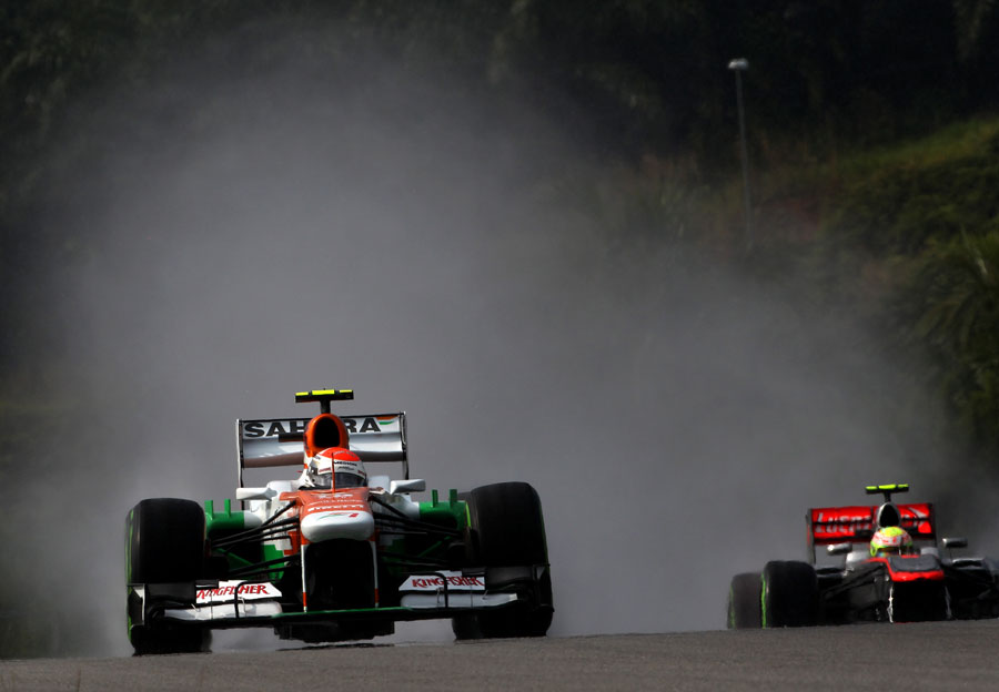 Adrian Sutil leads Sergio Perez in the wet