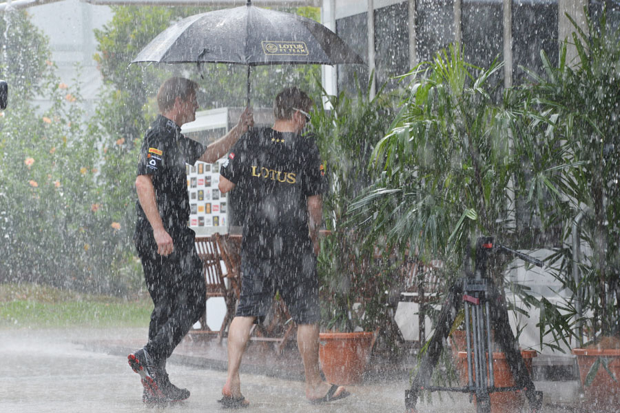 Kimi Raikkonen tries to shelter from a torrential downpour