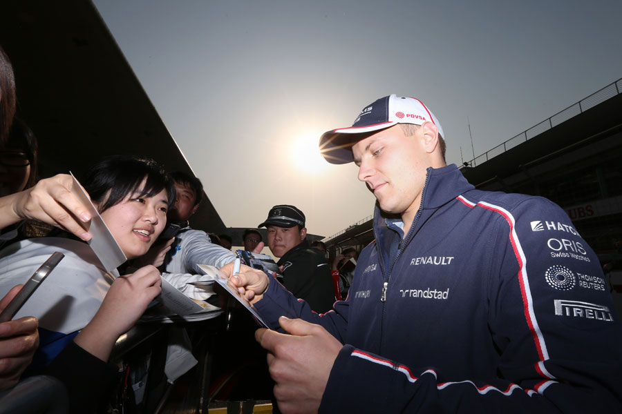 Valtteri Bottas signs autographs in the paddock
