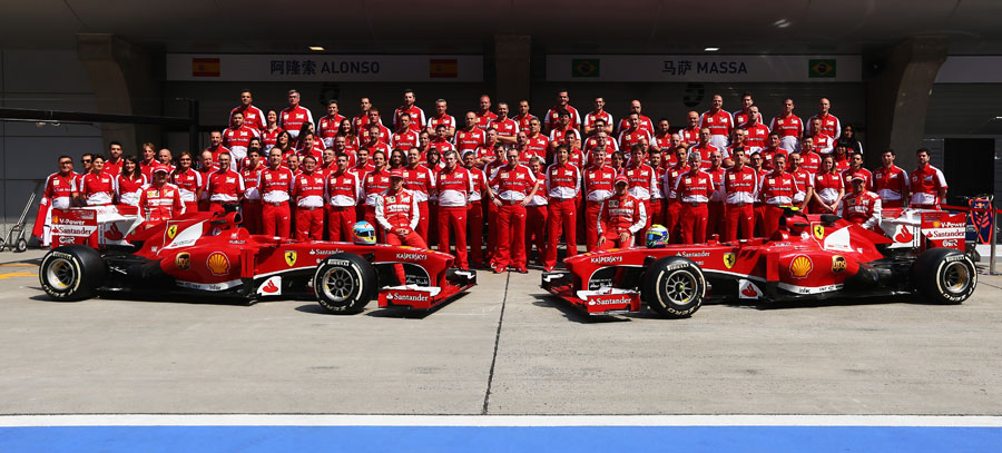 Ferrari pose for a team photo in the pit lane