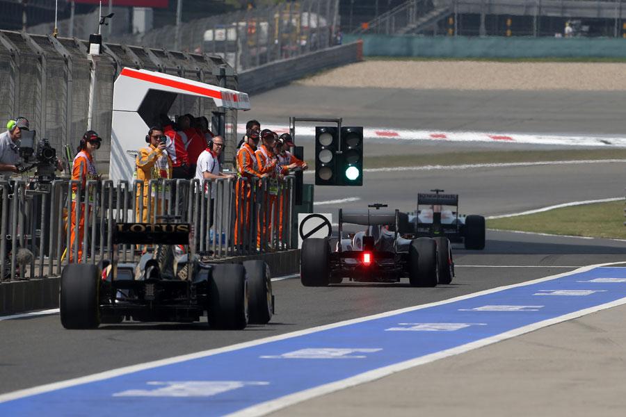 Nico Hulkenberg leads Kimi Raikkonen down the pit lane